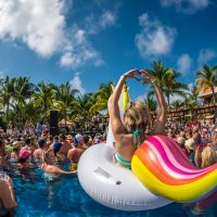 Girl on unicorn float in pool at Crash My Playa